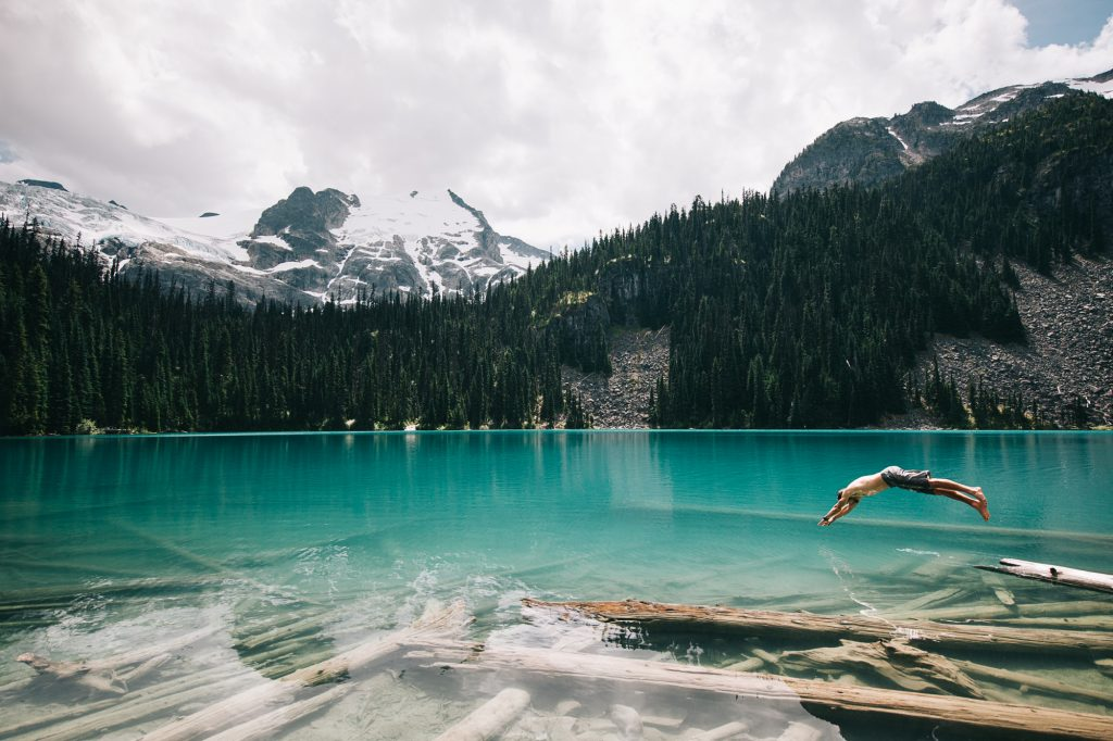 The photographer jumping into glacial lake